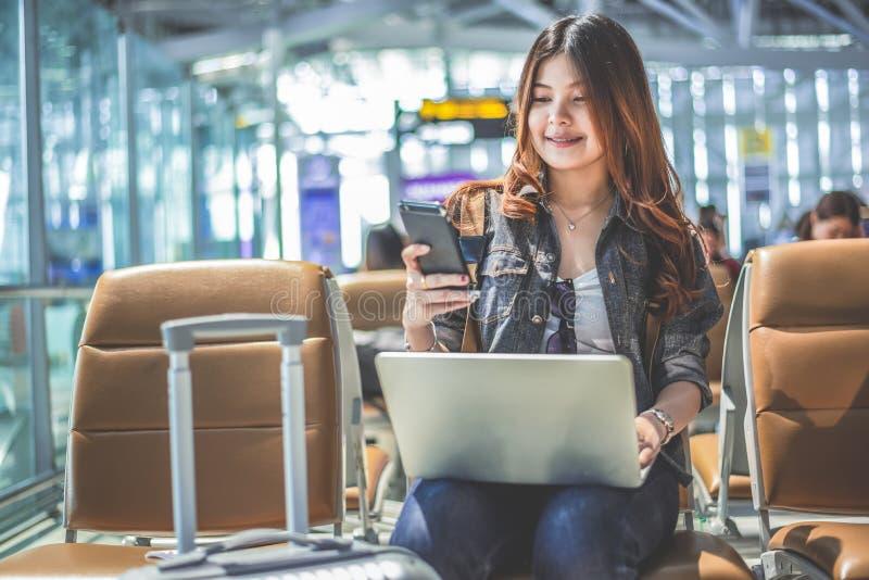 Giovane passeggero femminile asiatico che usando attimo dello Smart Phone e del computer portatile fotografie stock libere da diritti
