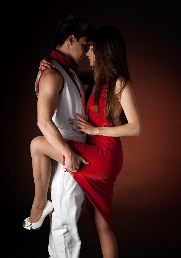 Giovane passione di dancing delle coppie su indicatore luminoso rosso scuro fotografie stock libere da diritti