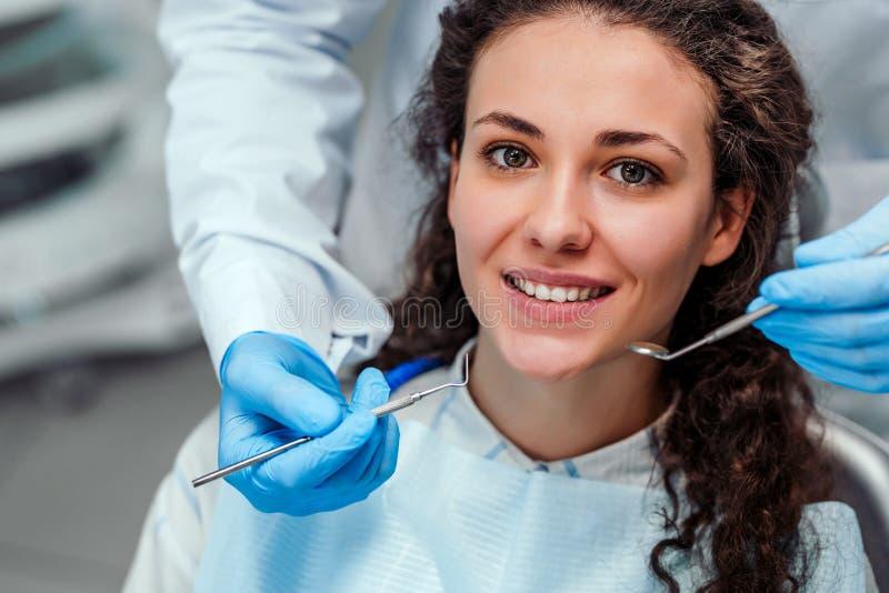 Giovane paziente femminile che si siede sulla sedia in ufficio dentario Preparando per l'esame dentario esaminando macchina fotog fotografie stock