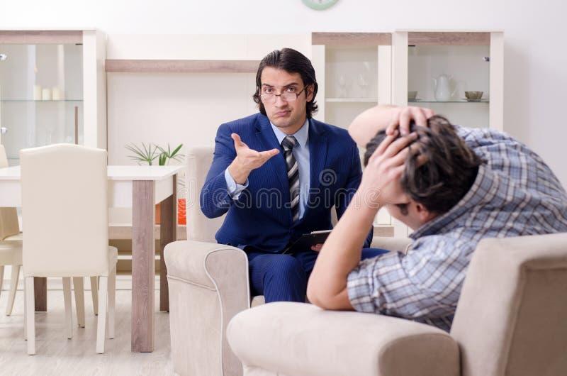 Giovane paziente maschio che discute con il problema personale dello psicologo fotografie stock