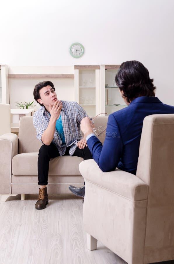 Giovane paziente maschio che discute con il problema personale dello psicologo immagini stock