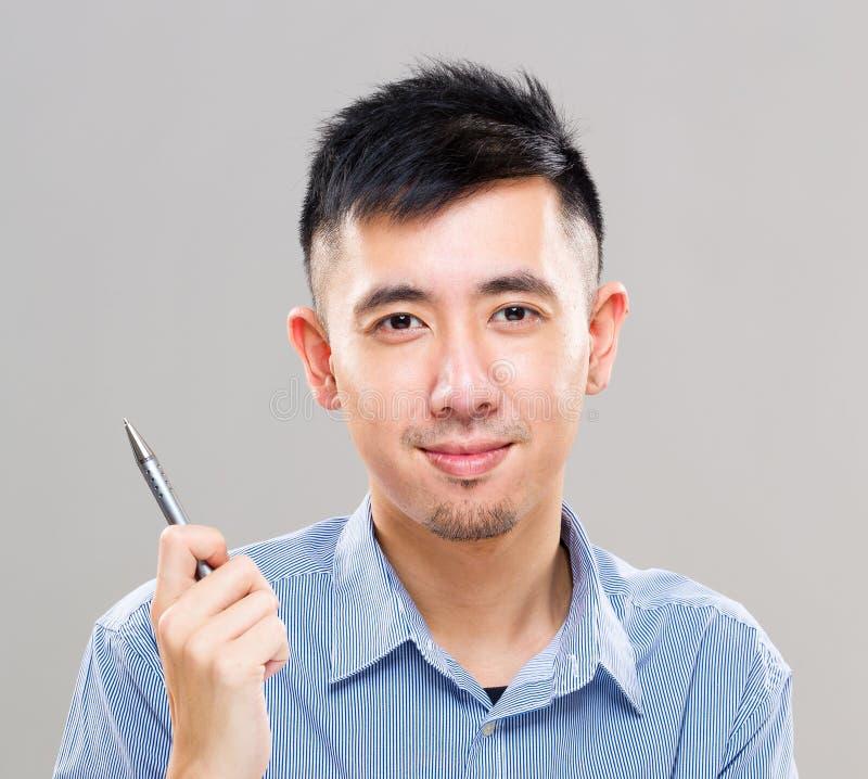 Giovane penna di tenuta asiatica dell'uomo fotografie stock