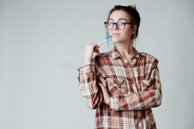 Giovane penna di tenuta castana sveglia della ragazza e riflettere, sembranti premurose fotografia stock libera da diritti