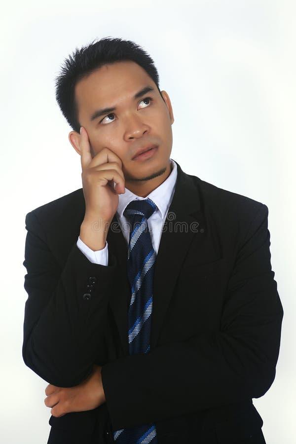 Giovane pensiero asiatico attraente bello dell'uomo d'affari immagini stock