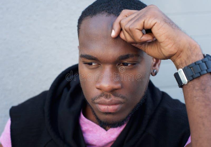 Giovane pensiero bello dell'uomo di colore fotografia stock libera da diritti
