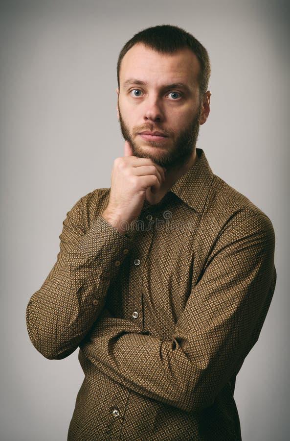Giovane pensieroso con la barba che esamina macchina fotografica fotografie stock libere da diritti