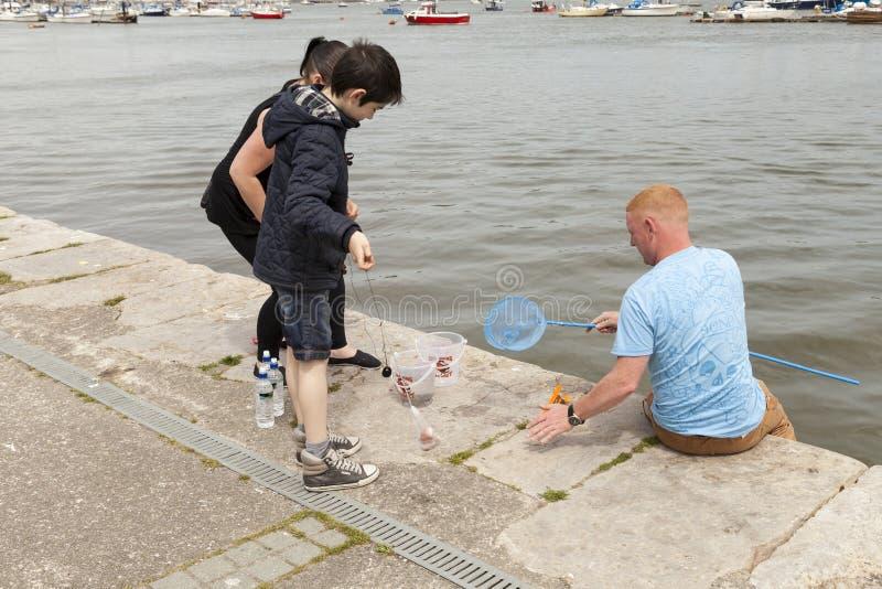 Giovane pesca del granchio della famiglia dal lato della banchina in Conwy fotografia stock