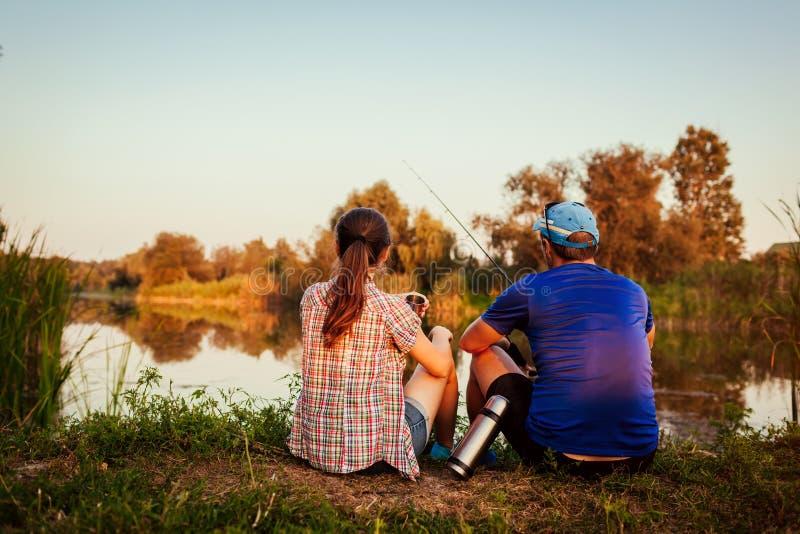 Giovane pesca delle coppie e tè bevente sul fiume al tramonto La gente che si rilassa e che raffredda all'aperto immagine stock