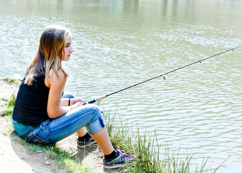 Giovane pesca teenager su una banca di fiume immagini stock