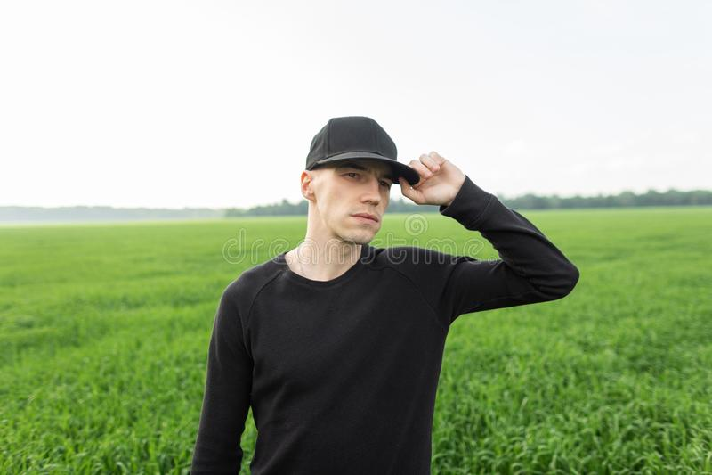 Giovane piacevole moderno in un berretto nero alla moda in una camicia nera alla moda che posa fra l'erba verde in un campo fuori immagini stock libere da diritti