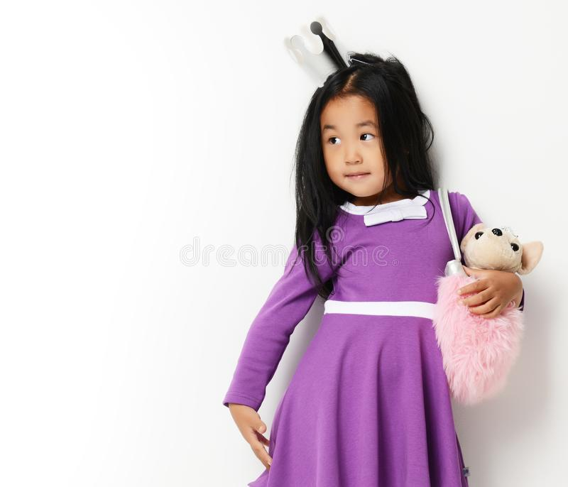 Giovane piccola ragazza asiatica felice del bambino pronta per il compleanno con il piccolo cane in borsa che esamina l'angolo immagine stock libera da diritti