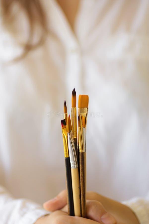 Giovane pittore caucasico dell'artista della donna nel mazzo disponibile della tenuta bianca della camicia di tipi differenti di  fotografia stock libera da diritti