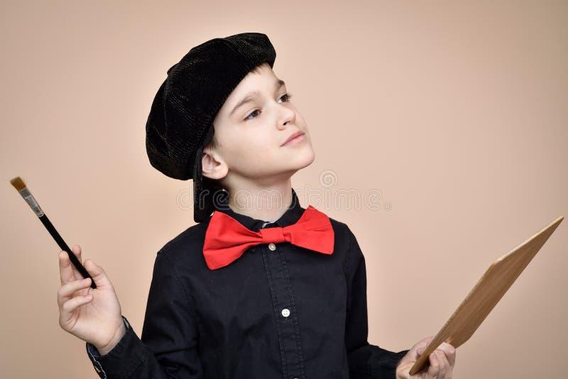 Giovane pittore con il farfallino rosso ed il pennello nero della tenuta del cappuccio e della camicia e la tavolozza di arte fotografie stock