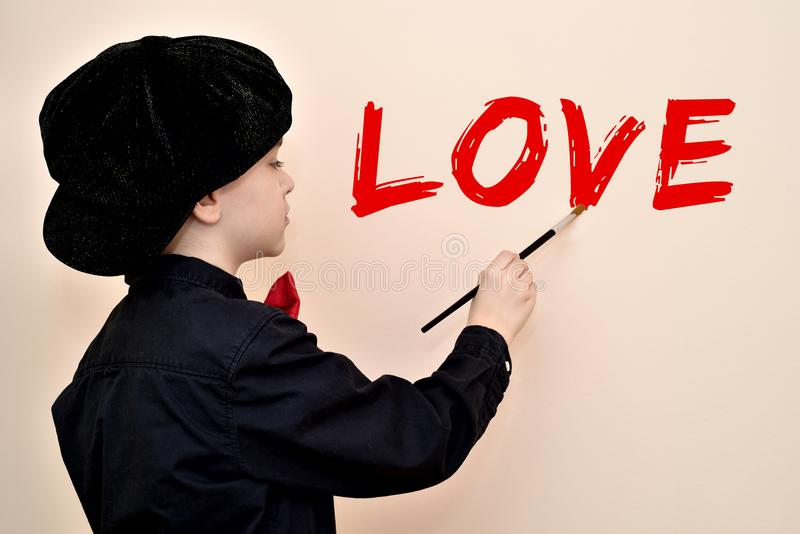 Giovane pittore con l'AMORE di scrittura della spazzola sulla parete fotografia stock libera da diritti