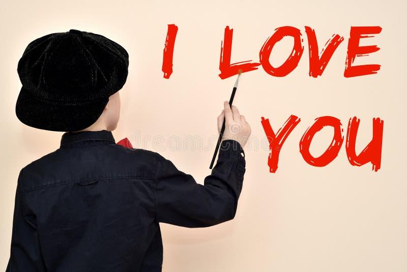 Giovane pittore con la spazzola che scrive TI AMO sulla parete immagine stock