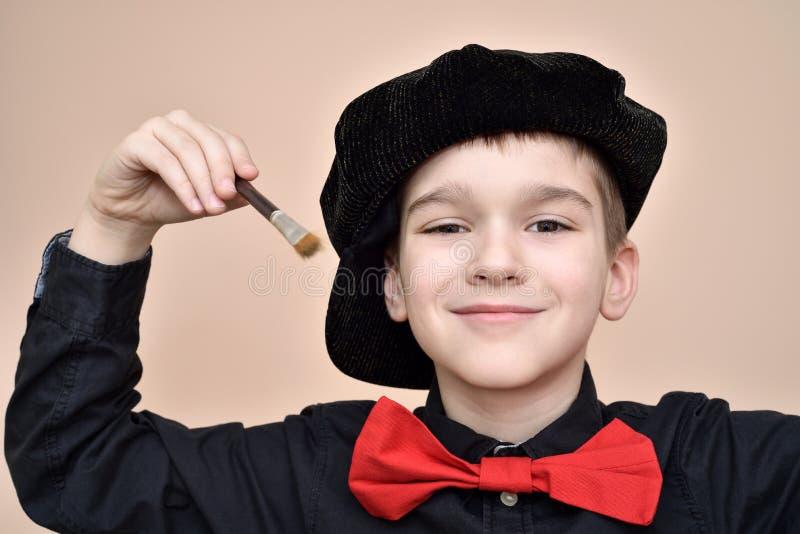 Giovane pittore sorridente con il farfallino rosso ed il pennello nero della tenuta del cappuccio e della camicia fotografie stock libere da diritti