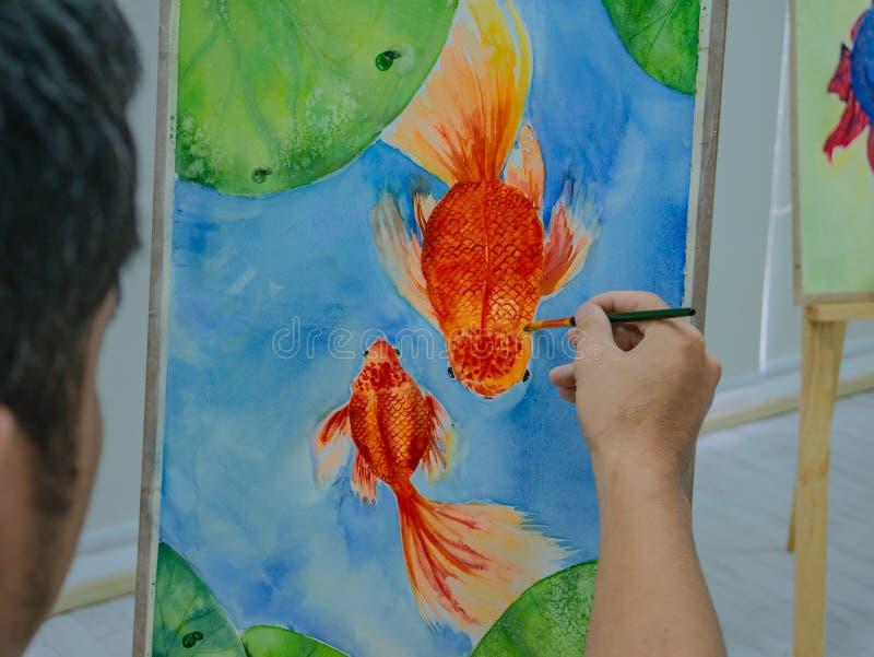 Giovane pittura maschio del pesce dell'acquerello del disegno dell'artista fotografia stock