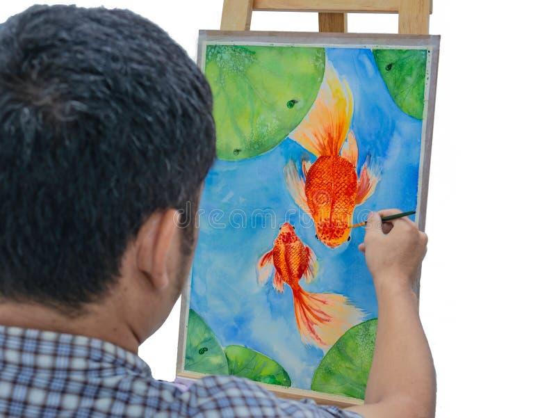 Giovane pittura maschio del pesce dell'acquerello del disegno dell'artista immagine stock