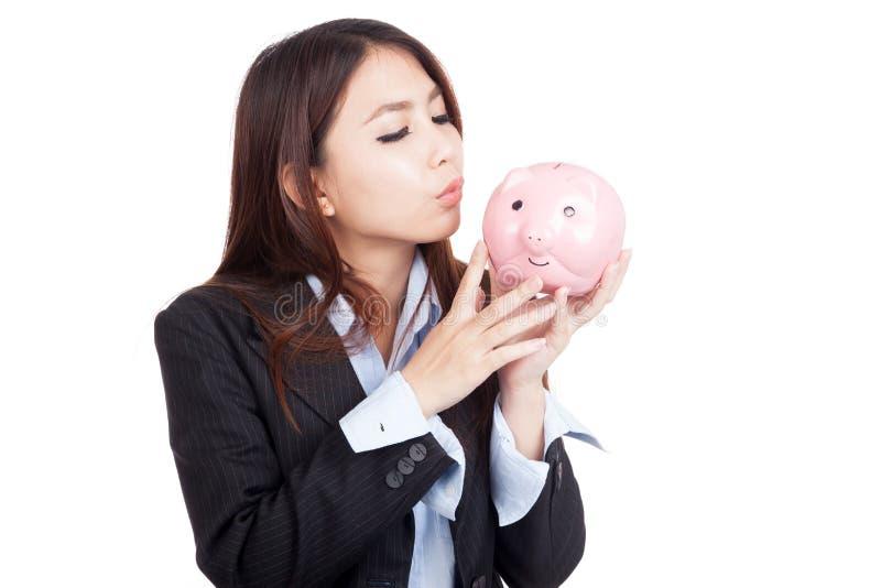 Giovane porcellino salvadanaio asiatico di bacio della donna di affari fotografie stock