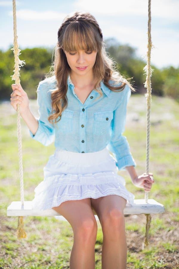 Giovane posa di modello pensierosa mentre sedendosi sull'oscillazione fotografie stock libere da diritti