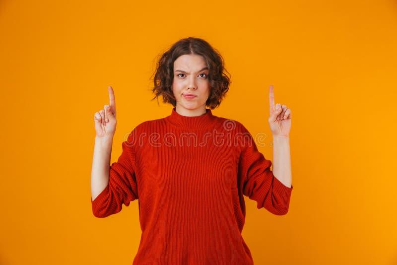 Giovane posa graziosa confusa della donna isolata sopra indicare giallo del fondo della parete immagine stock libera da diritti