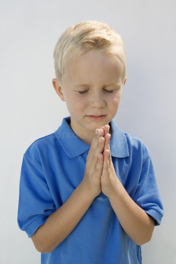 Giovane pregare del ragazzo fotografia stock libera da diritti
