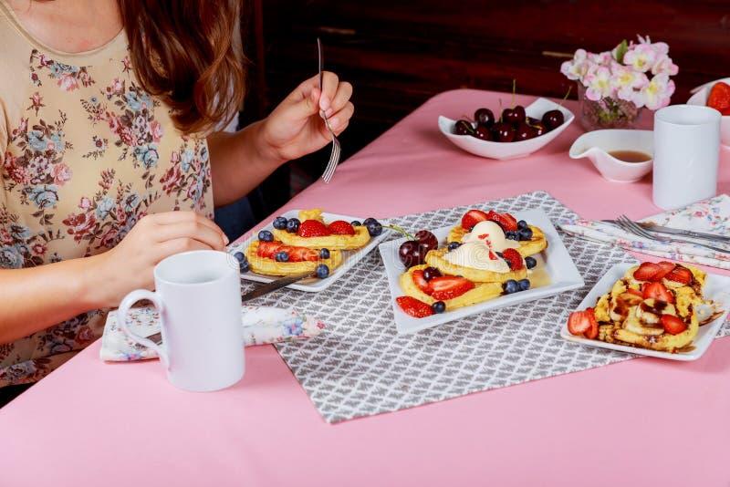 Giovane prima colazione graziosa della donna delle cialde con un tavolino da salotto nel salone immagine stock
