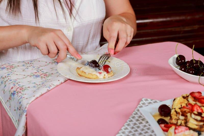 Giovane prima colazione graziosa della donna delle cialde con un tavolino da salotto nel salone fotografie stock libere da diritti