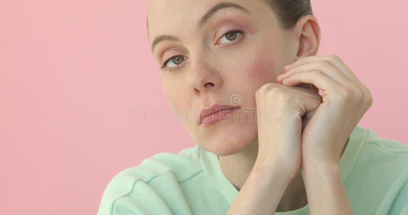 Giovane primo piano annoiato della donna a fondo rosa immagine stock