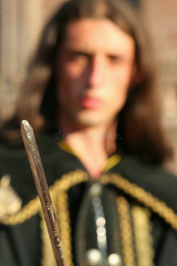 Giovane principe medioevale con il saber ed il mantello nero immagini stock