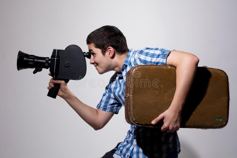 Giovane produttore cinematografico maschio con la vecchia cinepresa e una valigia nel suo fotografia stock libera da diritti
