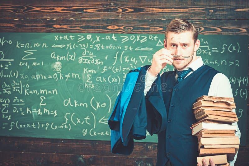 Giovane professore biondo che mette sui suoi vetri Uomo intelligente nel mucchio della tenuta del vestito dei libri immagine stock libera da diritti