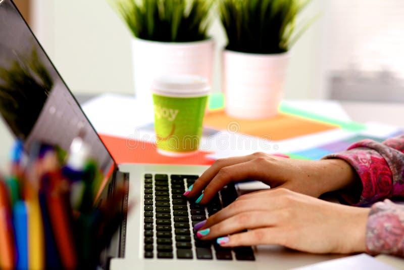 Giovane progettista che lavora al suo scrittorio con un computer fotografie stock