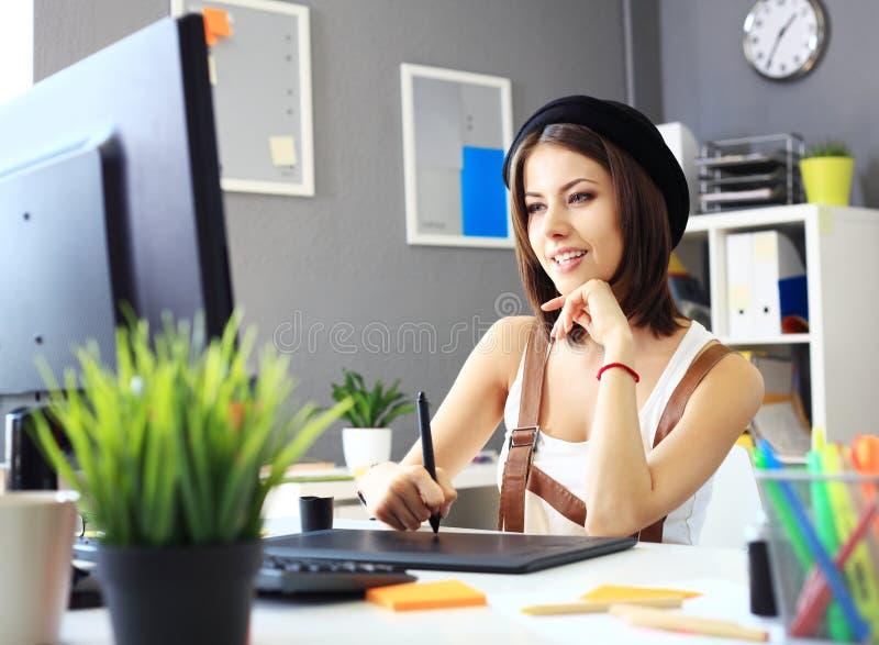 Giovane progettista femminile che per mezzo della tavola dei grafici mentre lavorando fotografia stock libera da diritti