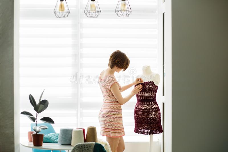 Giovane progettista femminile dell'abbigliamento che usando il manichino del vestito allo stile di vita interno e indipendente do fotografia stock libera da diritti