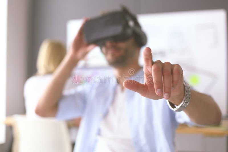 Giovane programmatore maschio del software che verifica un nuovo app con i vetri di realt? virtuale 3d in ufficio fotografie stock libere da diritti
