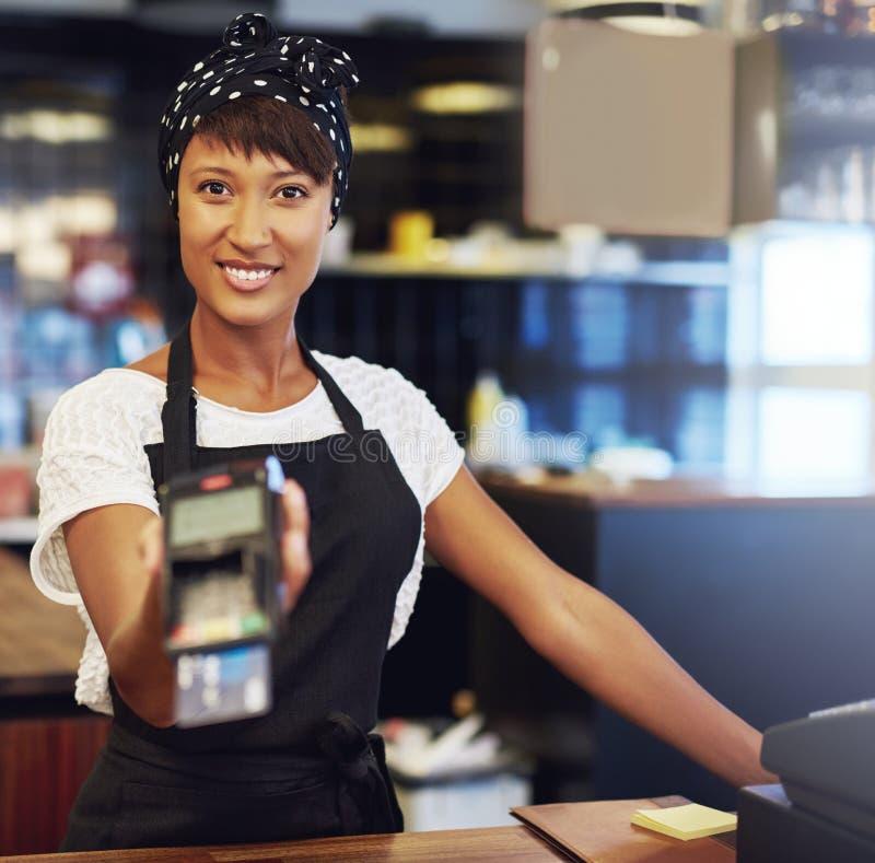 Giovane proprietario di negozio che richiede pagamento fotografia stock