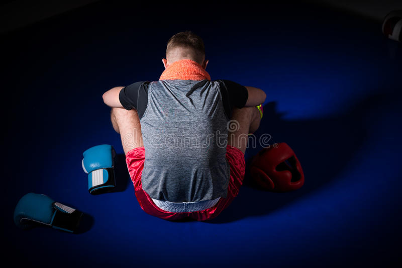 Giovane pugile maschio atletico con un asciugamano intorno al suo collo che si siede b immagine stock libera da diritti