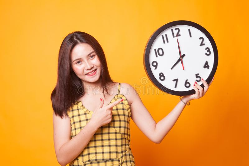 Giovane punto asiatico della donna ad un orologio immagini stock libere da diritti