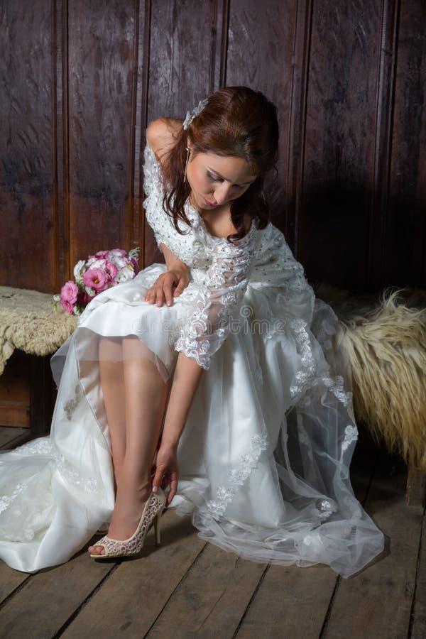 Giovane puttong della sposa sulle sue scarpe di nozze fotografia stock libera da diritti