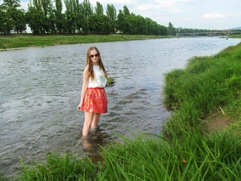 Giovane ragazza adulta con capelli biondi lunghi knee-deep in acqua e negli sguardi alla macchina fotografica immagini stock