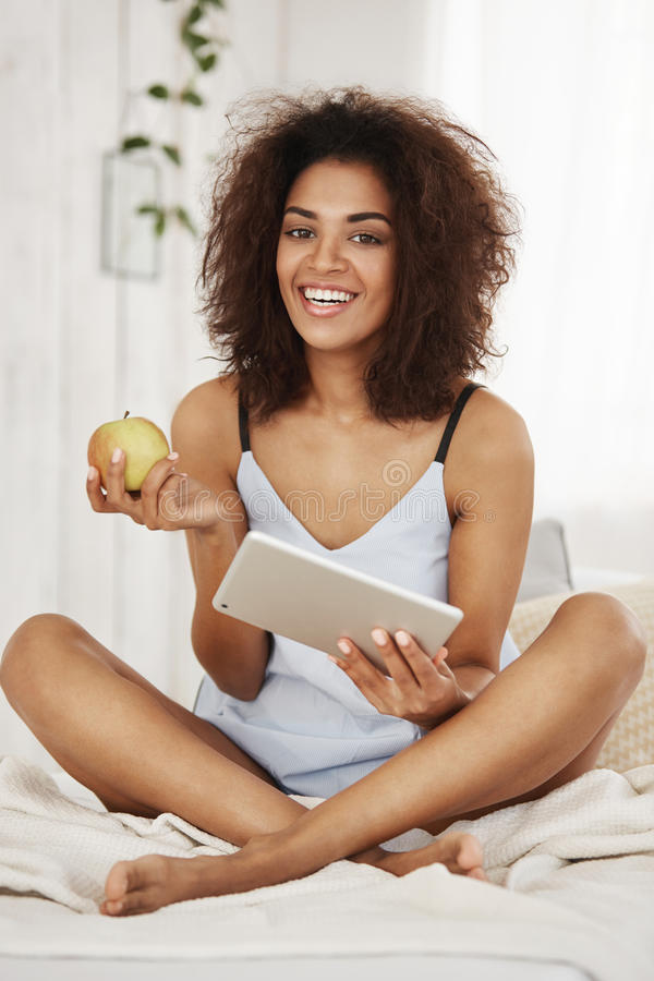 Giovane ragazza africana attraente in indumenti da notte o pigiami che si siedono sul letto che sorride esaminando la compressa e immagini stock libere da diritti