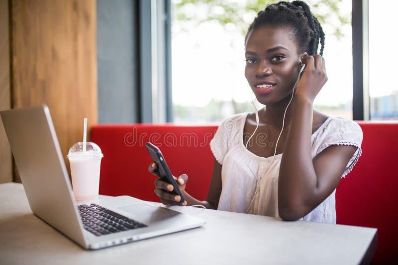 Giovane ragazza afroamericana che si siede nel ristorante con il computer portatile Ragazza graziosa con le cuffie allegro che es fotografie stock libere da diritti