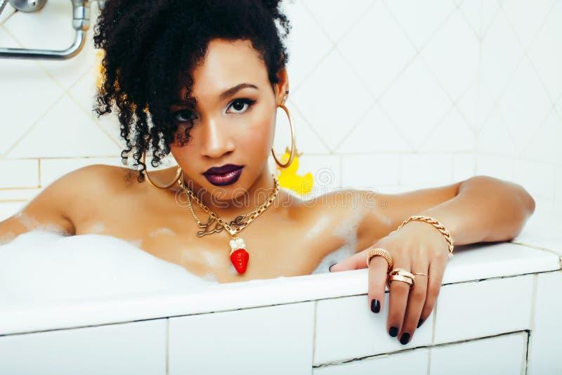 Giovane ragazza afroamericana graziosa che prende bagno con schiuma, concetto della gente di stile di vita fotografia stock libera da diritti