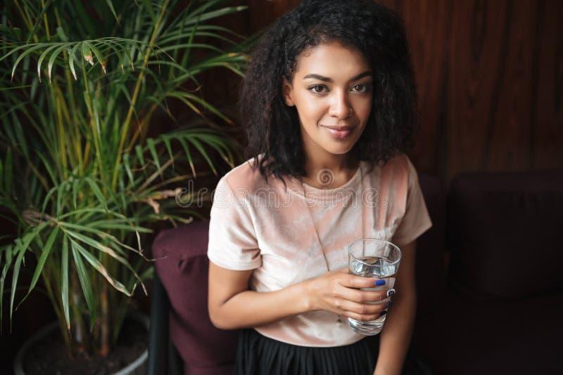 Giovane ragazza afroamericana sorridente che si siede nel ristorante e che guarda in camera Bella signora con capelli ricci scuri fotografia stock libera da diritti