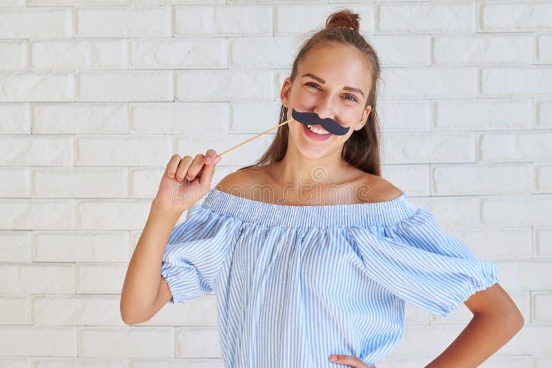 Giovane ragazza alla moda allegra che posa con i baffi di carta sullo sti fotografie stock libere da diritti