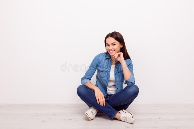 Giovane ragazza allegra attraente che tocca il suo mento e che si siede o fotografia stock libera da diritti