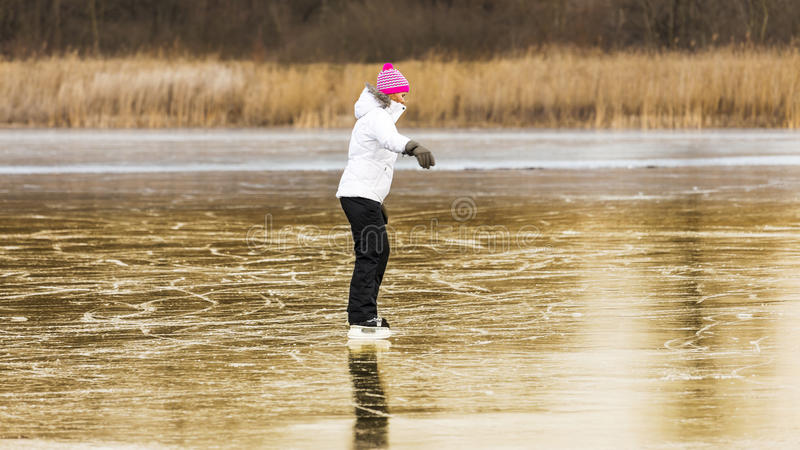 Giovane ragazza allegra che pattina sul lago fotografie stock