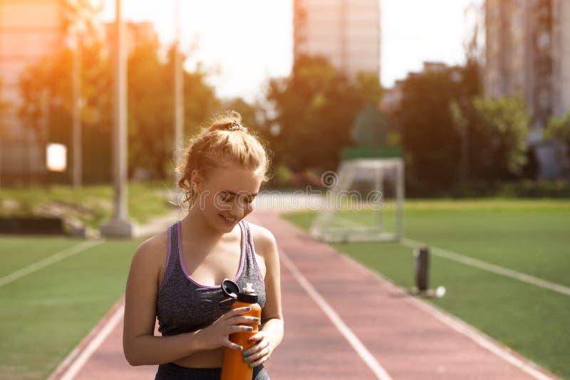 Giovane ragazza allegra con l'acconciatura riccia sullo stadio fotografie stock libere da diritti