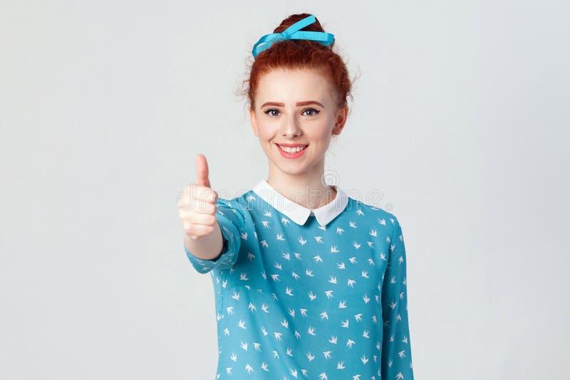 Giovane ragazza allegra felice della testarossa che mostra pollice su e sorriso a trentadue denti Studio sparato su fondo grigio fotografia stock